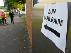 Ein Zettel mit der Aufschrift Zum Wahlraum hängt an einem eingerichteten Wahllokal in Hannover.
